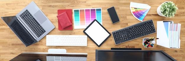 Les lieux de travail dans les chaises de table de bureau tablette palette de couleurs smartphone crayons moniteurs de clavier de tablette