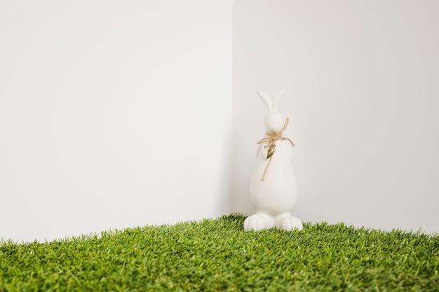 Lièvre avec une figurine d'arc sur l'herbe