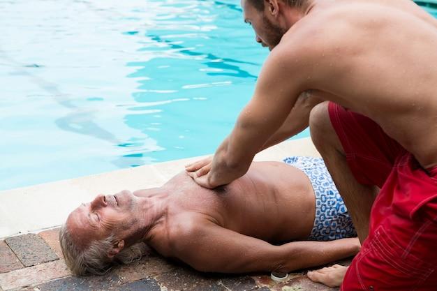 Lifeguard en appuyant sur la poitrine de l'homme senior inconscient au bord de la piscine