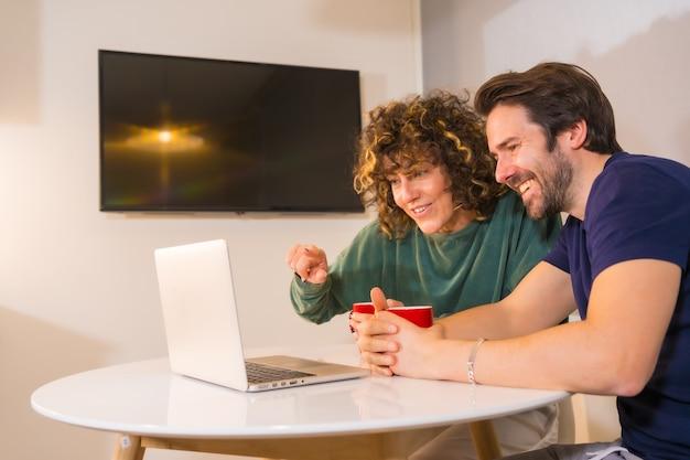 Lifestyle, à un jeune couple caucasien en pyjama prenant son petit déjeuner dans la cuisine, passant un appel vidéo familial sur l'ordinateur, une nouvelle normalité dans la pandémie de coronavirus