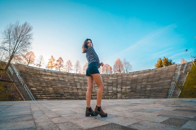 Lifestyle, une jeune femme avec pull rayé brune dansant dans un amphithéâtre