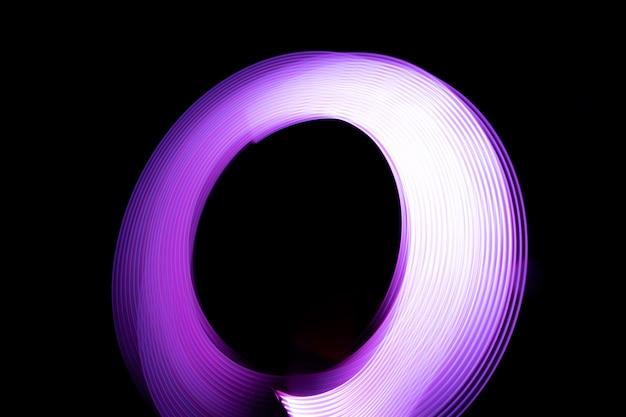 Light painting la nuit à l'aide de lumières. effet de lumière abstraite sur fond noir (photo).