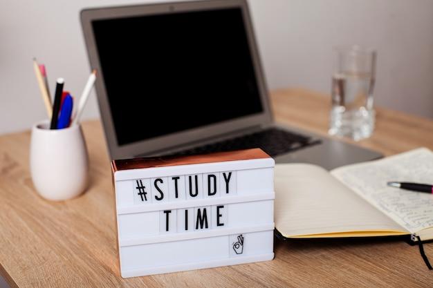Lightbox avec l'inscription temps d'étudier en arrière-plan est un ordinateur portable un ordinateur portable et un cahier ...