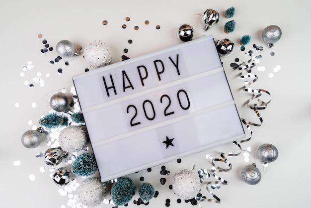 Lightbox lettre blanche avec happy 2020 entouré de décorations de noël