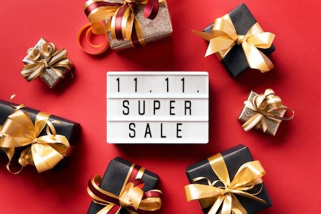 Lightbox avec texte et boîtes noires avec des arcs dorés sur fond rouge. journée des célibataires 11.11. concept. achats en ligne de chine.
