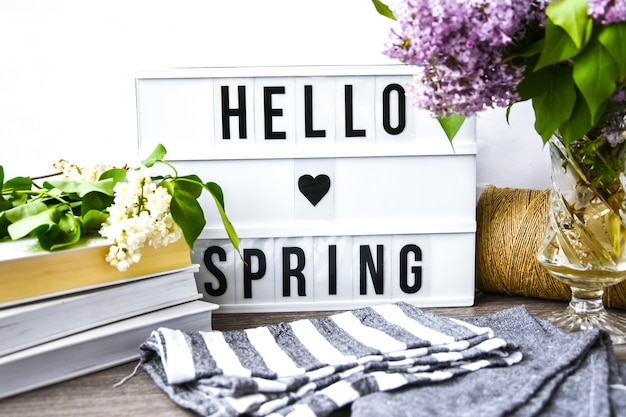 Lightbox avec texte bonjour printemps et bouquet de fleurs lilas violet dans un vase en verre