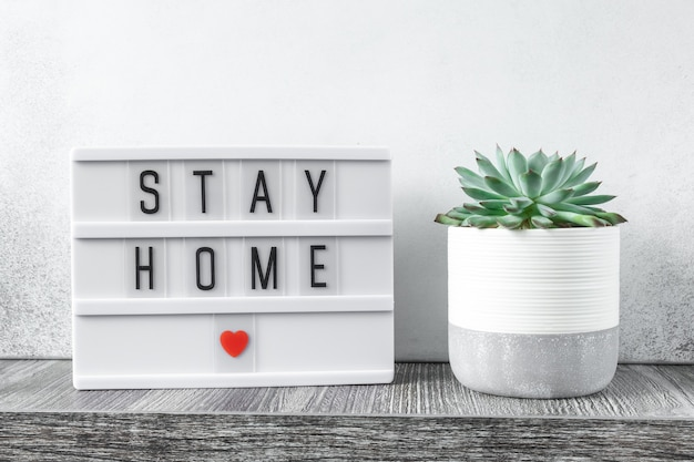Lightbox avec texte rester à la maison et plantes de cactus sur table en bois. restez en sécurité, restez à l'intérieur du concept de maison