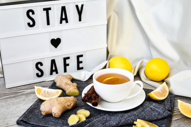 Lightbox avec texte restez en sécurité gingembre stimulant l'immunité chaude boisson naturelle vitaminée avec agrumes, miel et ingrédients dans un style rustique sur fond en bois. thé à la camomille. concept sain