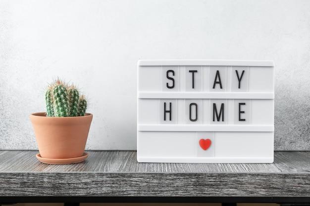 Lightbox avec texte stay home et plante à la maison en pot en céramique sur table en bois stay home concept