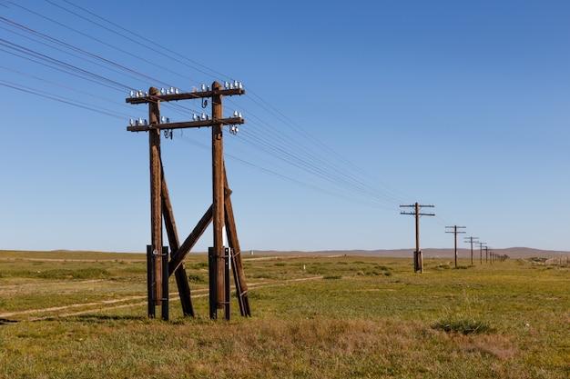 Ligne aérienne sur des supports en bois dans la steppe mongole