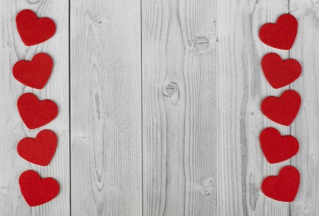 Ligne de coeurs rouges sur les côtés d'un fond en bois blanc et gris. concept de la saint-valentin