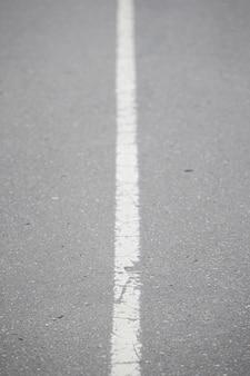 Ligne continue blanche sur asphalte
