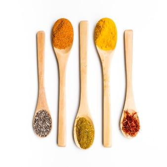 Ligne de cuillères en bois remplies d'épices