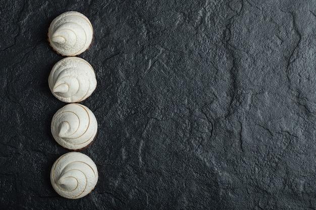 Une ligne de délicieux cupcakes sur fond sombre.