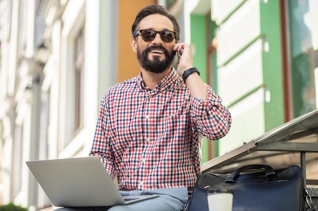 Ligne directe. enthousiaste homme souriant, parler sur smartphone tout en utilisant son ordinateur portable à l'extérieur