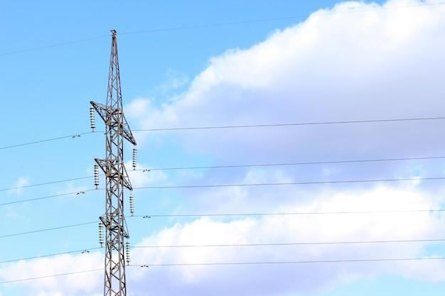 Ligne électrique contre le ciel bleu avec des fils de centrale électrique de nuages