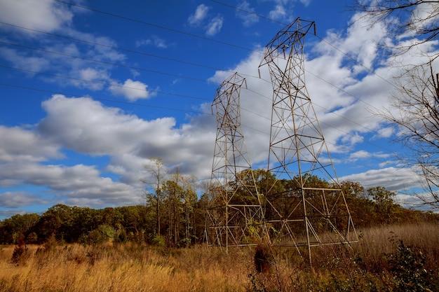 Ligne électrique contre les lignes électriques de nuages de ciel d'automne de ciel bleu lumineux