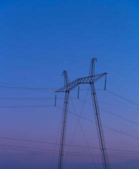 Ligne électrique à haute tension contre le ciel bleu