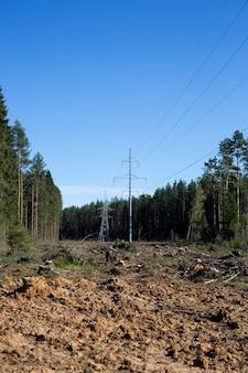 Ligne électrique à haute tension dans la forêt. la déforestation pour le progrès moderne. dommages environnementaux causés par l'homme