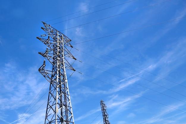 Ligne électrique haute tension sur fond de ciel bleu.