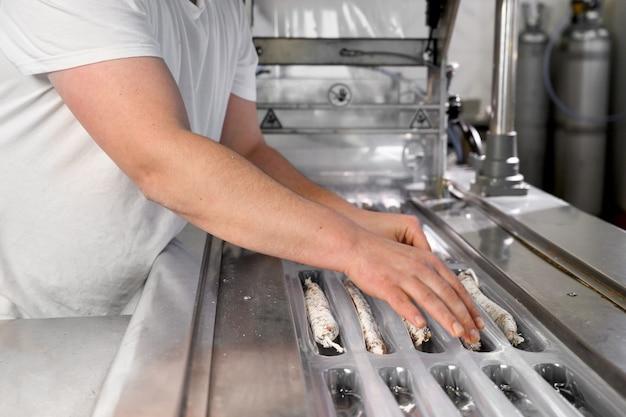 La ligne d'emballage de saucisses de saucisses fuet est une saucisse sèche catalane fine de viande de porc dans une fabrication industrielle d'intestin de porc de produits de saucisse