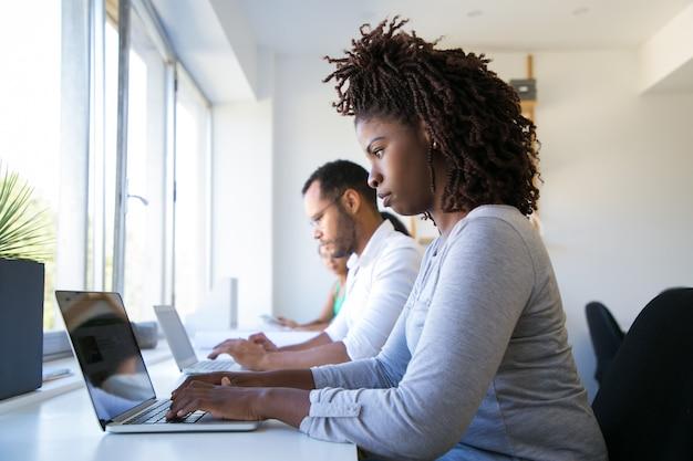 Ligne d'employés travaillant sur des gadgets numériques