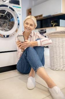 En ligne. femme au foyer blonde en chemise rayée assis près de la machine à laver et lire quelque chose en ligne