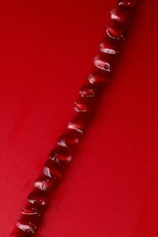 Ligne de graines de grenade juteuses fraîches mûres rubis close up isolé sur fond rouge avec espace de copie