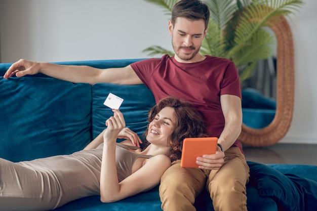 En ligne. un homme et une femme assise sur le canapé avec un ordinateur portable