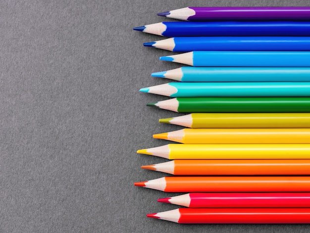 Ligne horizontale de crayons de couleur sur papier gris.