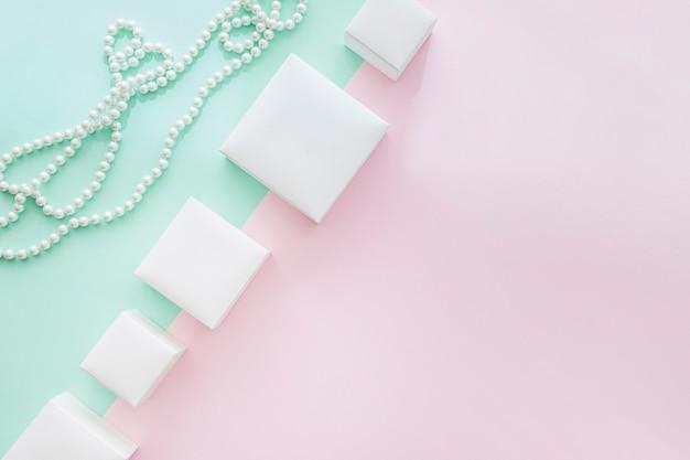 Ligne d'inclinaison de différentes boîtes blanches avec collier de perles sur fond pastel
