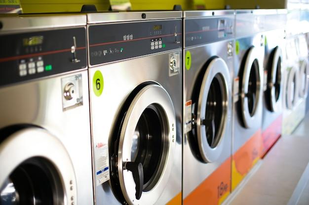 Ligne de machines à laver industrielles dans une laverie publique.