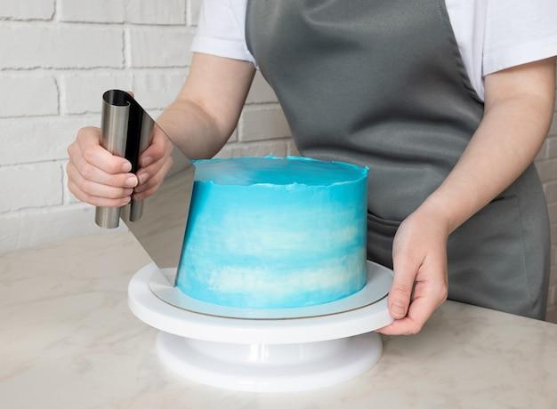 Ligne de mains de fille avec une spatule à crème sur un gâteau rond. décorer le gâteau des fêtes.
