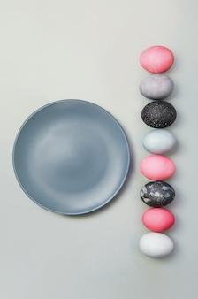 Ligne d'oeufs de pâques colorés près de la plaque bleue