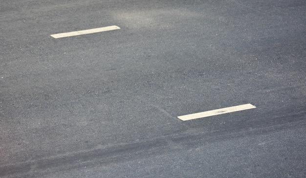 Ligne de peinture blanche sur asphalte noir. fond de transport spatial