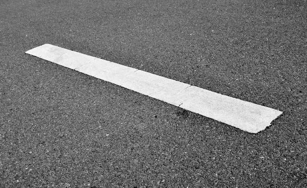 Ligne de peinture blanche sur asphalte noir.