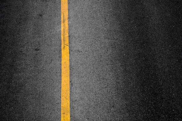 Ligne de peinture jaune sur asphalte noir.