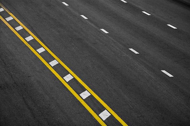 Ligne de peinture jaune et blanche sur asphalte noir