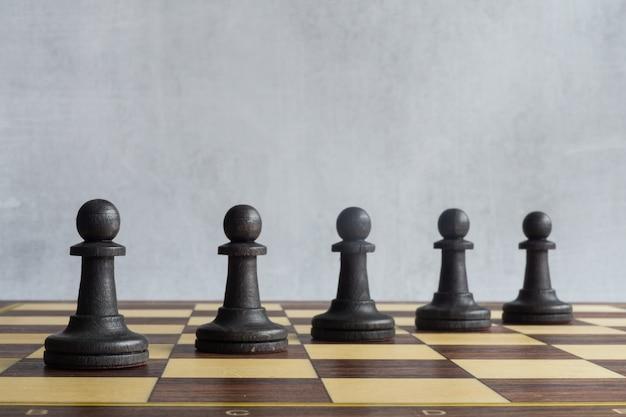 Une ligne de pions d'échecs noirs sur le plateau