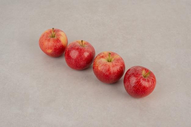 Ligne de pommes rouges sur fond blanc.