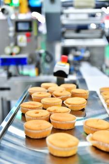 Ligne de production automatique de muffins de boulangerie sur des machines d'équipement de bande transporteuse en usine, production alimentaire industrielle.