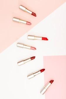 Ligne de rouges à lèvres métalliques sur fond pastel