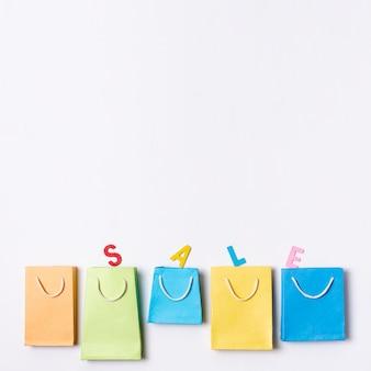 Ligne de sacs en papier de couleur avec concept de texte de vente