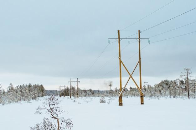 Ligne de transmission d'énergie en hiver jour de neige. concept de transport d'électricité