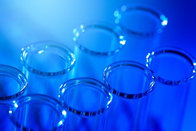 Ligne de tubes à essai. concept de laboratoire médical ou scientifique, gouttelette de liquide avec compte-gouttes sur fond bleu, gros plan, photo de micro photographie.