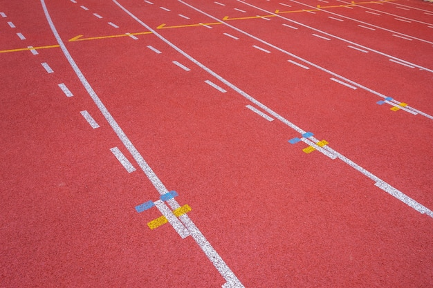 Lignes blanches du stade et texture des pistes de course en caoutchouc rouge