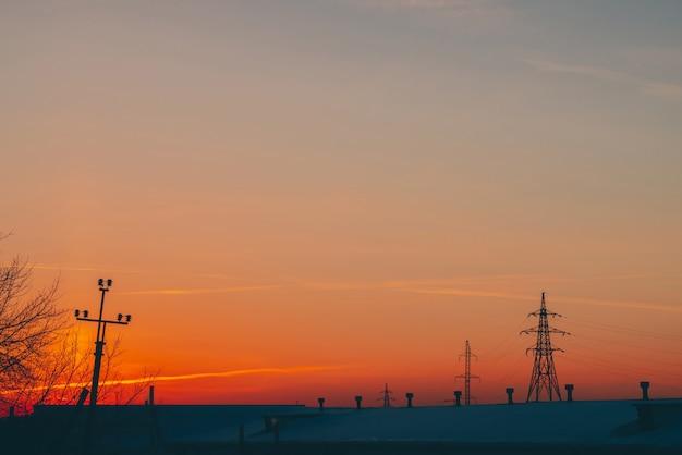 Lignes électriques au-dessus du toit à l'aube.