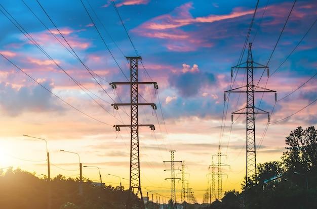 Lignes électriques, ciel du soir au coucher du soleil et rue en perspective dans la ville.