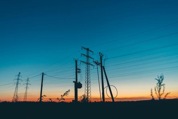 Lignes électriques dans le champ au lever du soleil