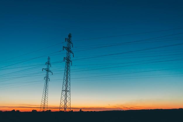 Lignes électriques dans le champ sur le ciel de lever du soleil.